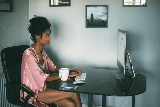 Mulher negra em casa trabalhando com computador e café da manhã