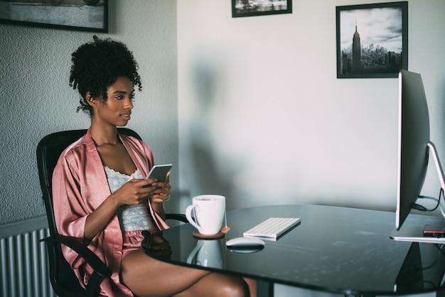Mulher negra em casa trabalhando com computador, smartphone e café pela manhã