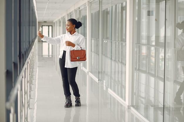 Mulher negra em pé no escritório com um laptop