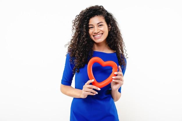 Mulher negra em um vestido azul com forma de coração vermelho nas mãos isoladas