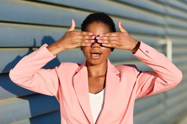 Mulher negra engraçada em pé na parede urbana, cobrindo os olhos com as mãos