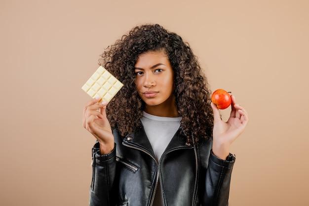 Mulher negra escolhe entre maçã e chocolate isolado sobre marrom
