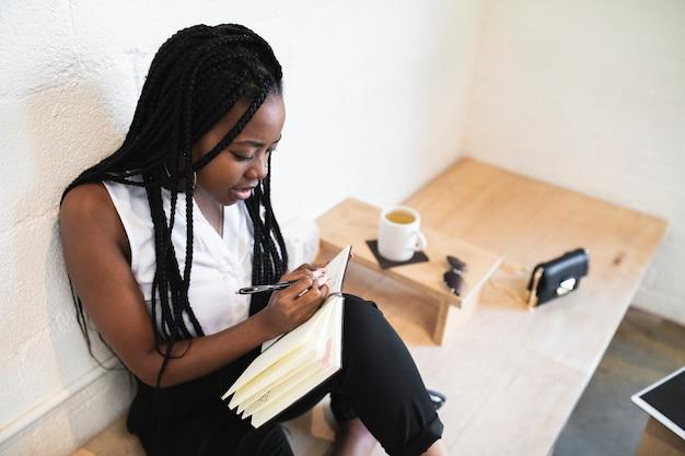 Mulher negra escrevendo em um caderno em um café