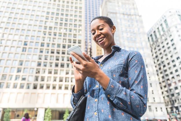Mulher negra, escrevendo no telefone na cidade