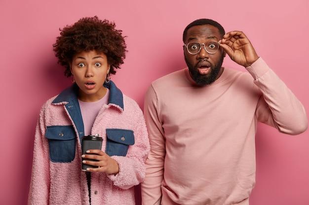 Mulher negra estupefata preocupada e homem confuso com a situação problemática, olhos bem abertos, bebem café aromático, usam roupas rosadas