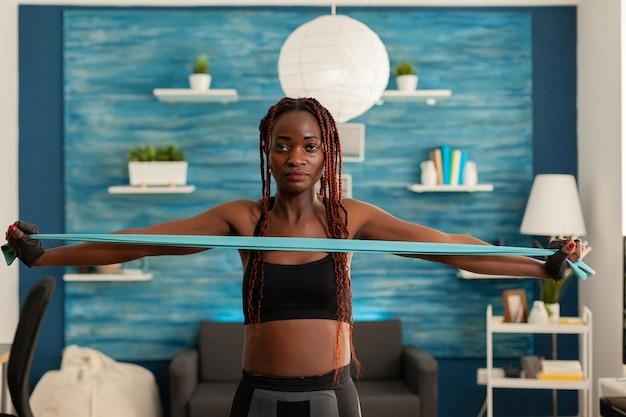 Mulher negra exercitando força muscular com elástico na sala de estar em casa para o corpo saudável africano ...