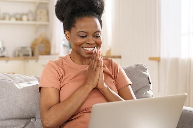 Mulher negra exultante olha para laptop animar e boa notícia. garota africana lendo e-mail ou mensagem no sofá