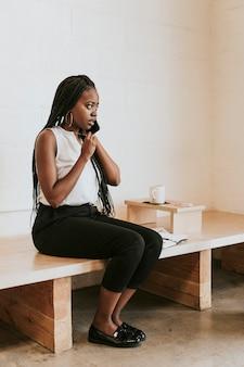 Mulher negra falando ao telefone em um café