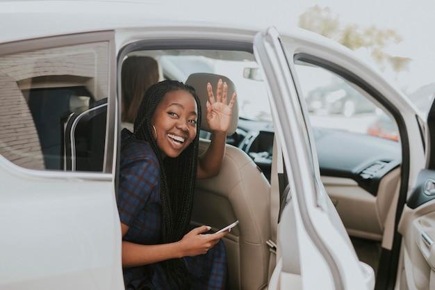 Mulher negra feliz acenando para se despedir de um carro
