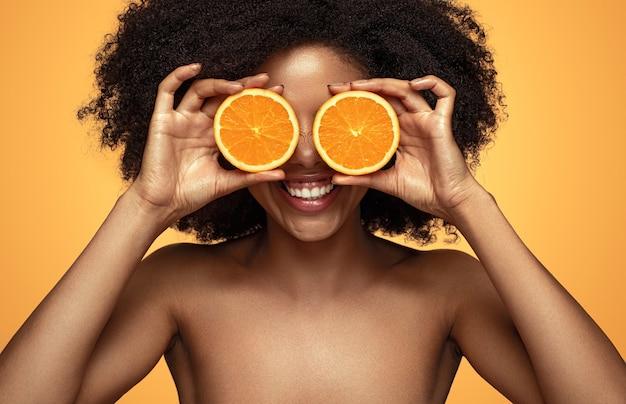 Mulher negra feliz brincando com laranja
