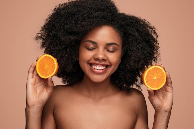 Mulher negra feliz com laranja madura