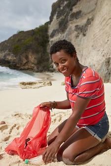 Mulher negra feliz com piercing carrega garrafa de plástico reciclável