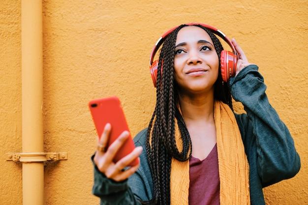 Mulher negra feliz com tranças ouvindo música com fones de ouvido