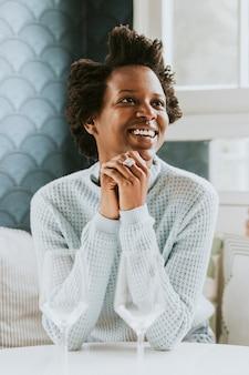 Mulher negra feliz com uma taça de vinho