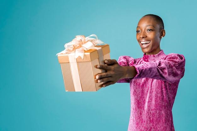 Mulher negra feliz dando um presente