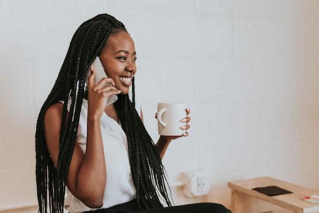 Mulher negra feliz falando ao telefone em um café