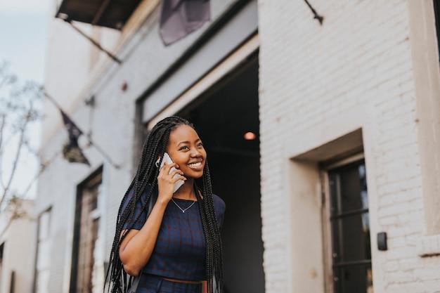 Mulher negra feliz falando ao telefone enquanto caminha pela rua