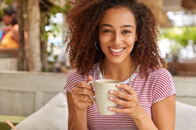 Mulher negra feliz segura uma caneca com uma bebida aromática quente, sorri positivamente, vestida com uma camiseta listrada, tem cabelo escuro e crespo, desfruta de uma conversa agradável com um amigo no restaurante