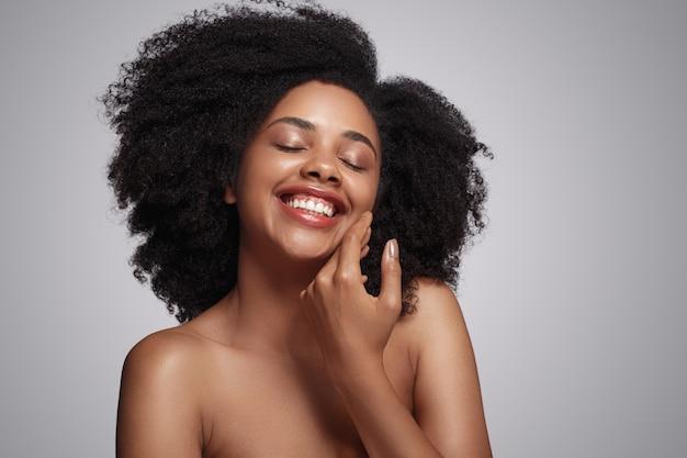Mulher negra feliz tocando a pele macia