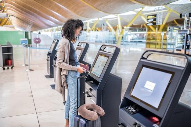 Mulher negra feliz usando a máquina de check-in no aeroporto, recebendo o cartão de embarque.
