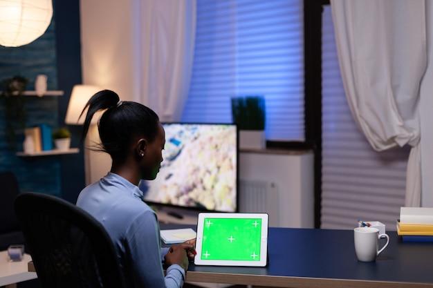 Mulher negra freelancer trabalhando em casa tarde da noite com dispositivo tendo cópia espaço disponível sentado no escritório. usando o computador de exibição chave de croma de maquete.