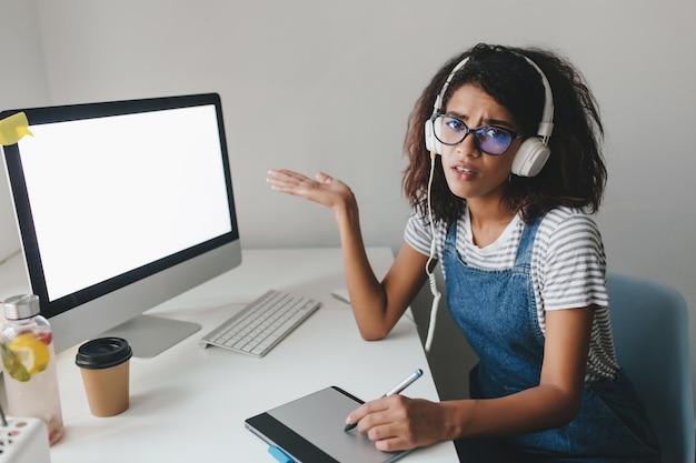 Mulher negra infeliz de macacão jeans apontando para a tela do computador e reclamando de internet ruim