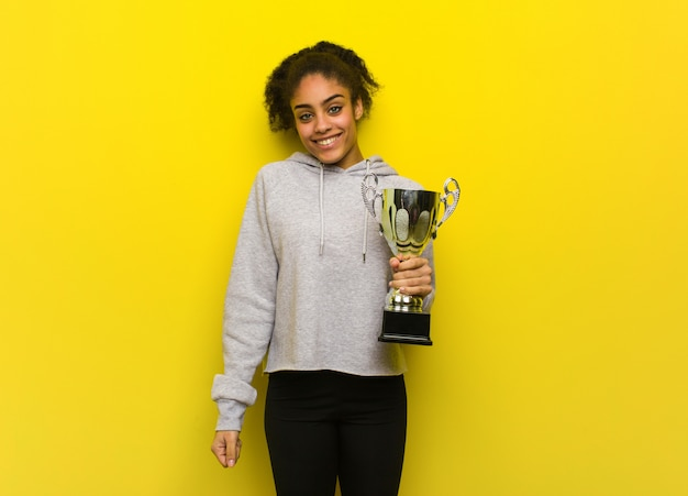Mulher negra jovem aptidão alegre com um grande sorriso. segurando um troféu.