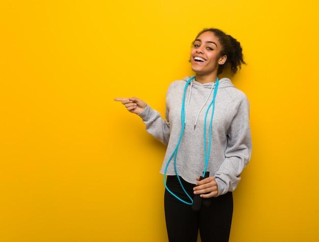 Mulher negra jovem aptidão apontando para o lado com o dedo. segurando uma corda de pular.