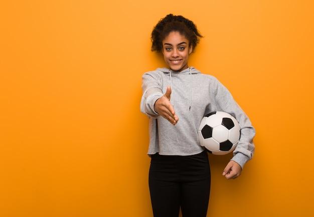 Mulher negra jovem aptidão chegando para cumprimentar alguém. segurando uma bola de futebol.