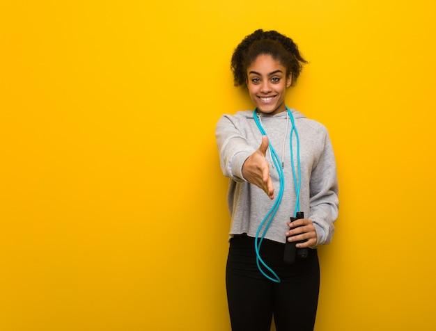 Mulher negra jovem aptidão chegando para cumprimentar alguém. segurando uma corda de pular.