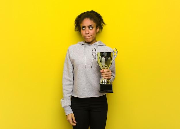 Mulher negra jovem aptidão pensando em uma idéia. segurando um troféu.