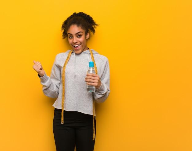 Mulher negra jovem aptidão sorrindo e apontando para o lado. segurando uma garrafa de água.