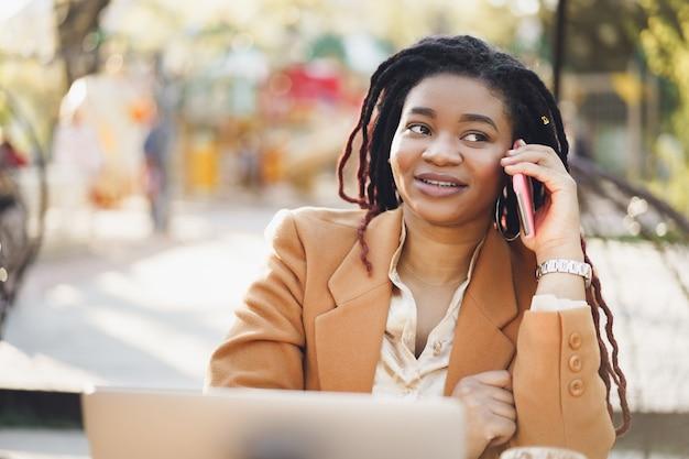 Mulher negra jovem e positiva sentada em um café ao ar livre e falando ao telefone