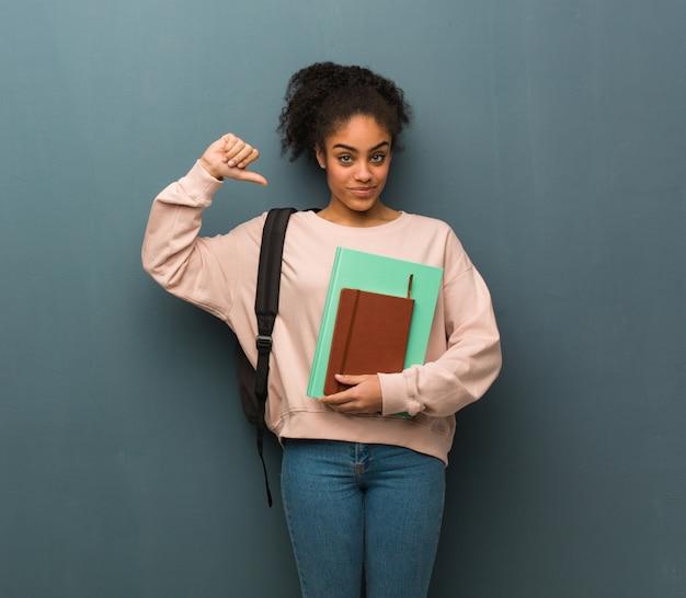 Mulher negra jovem estudante apontando os dedos, exemplo a seguir. ela está segurando livros.