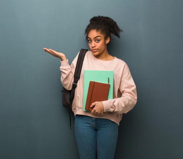 Mulher negra jovem estudante confusa e duvidosa. ela está segurando livros.