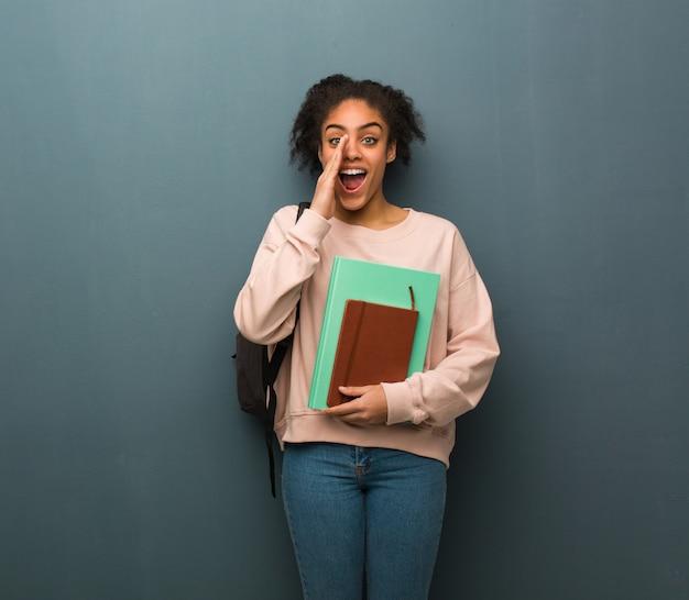 Mulher negra jovem estudante gritando algo feliz para a frente. ela está segurando livros.
