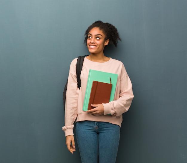 Mulher negra jovem estudante sonha em alcançar objetivos e finalidades. ela está segurando livros.