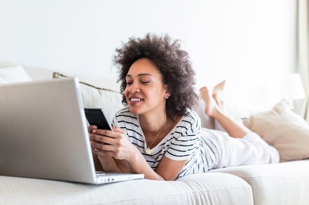 Mulher negra jovem feliz usando o celular enquanto está sentado em um sofá em casa com computador portátil.