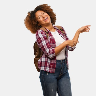 Mulher negra jovem viajante apontando para o lado com o dedo