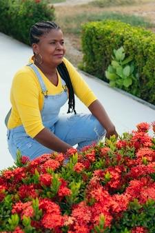 Mulher negra madura posando perto de flores vermelhas ao ar livre