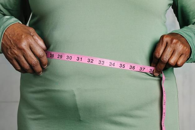Mulher negra medindo a barriga