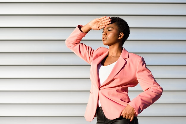 Mulher negra, modelo da moda, de pé na parede urbana