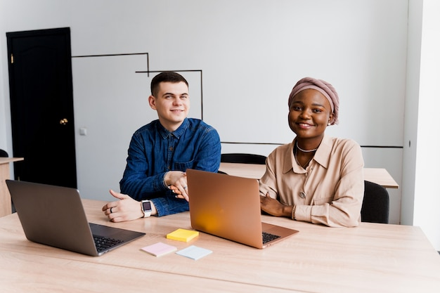 Mulher negra muçulmana e homem branco com laptop. casal multiétnico trabalha online juntos em projeto de negócios.