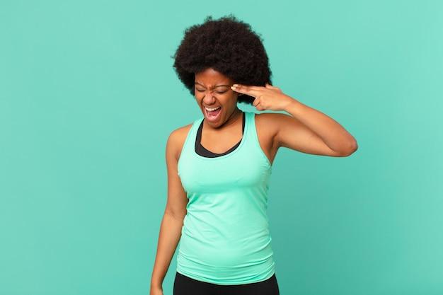 Mulher negra negra parecendo infeliz e estressada, gesto de suicídio fazendo sinal de arma com a mão, apontando para a cabeça