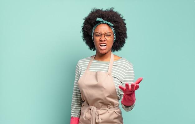 Mulher negra negra parecendo zangada, irritada e frustrada gritando wtf ou o que há de errado com você. conceito de limpeza. conceito doméstico