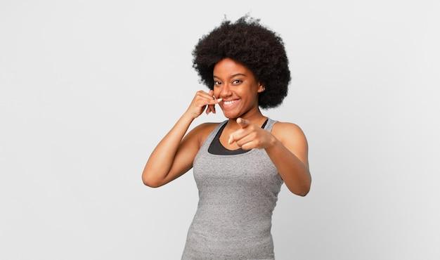 Mulher negra negra sorrindo alegremente e apontando para a câmera enquanto faz um gesto depois de ligar para você, falando ao telefone