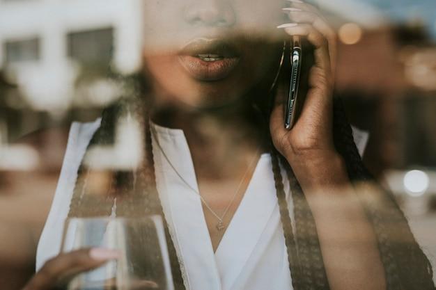 Mulher negra no telefone olhando pela janela