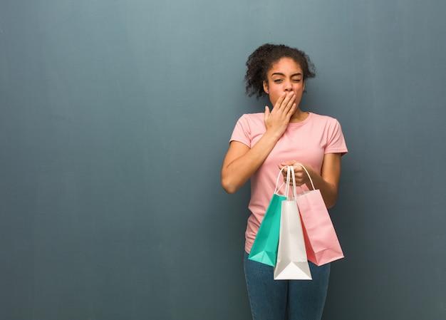 Mulher negra nova cansada e muito sonolento. ela está segurando uma sacola de compras.