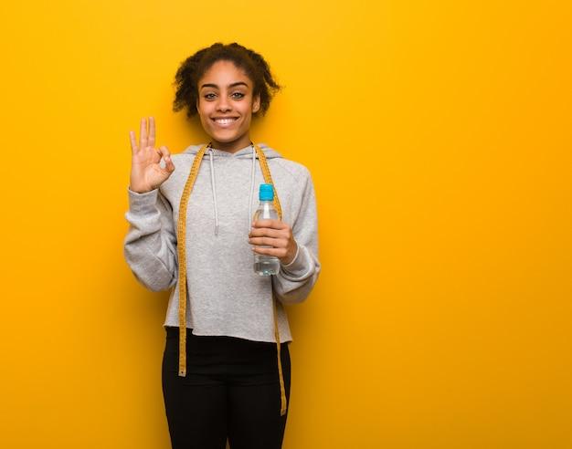 Mulher negra nova da aptidão alegre e segura fazendo o gesto aprovado. guardarando uma garrafa de água.
