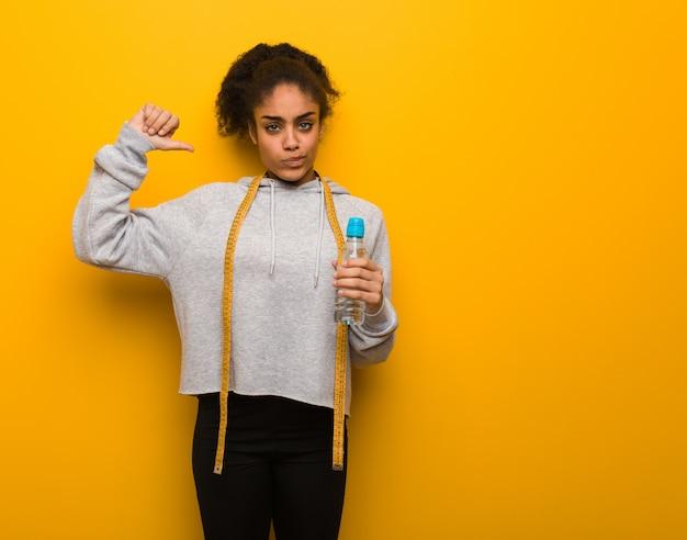 Mulher negra nova da aptidão que aponta os dedos, exemplo a seguir. guardarando uma garrafa de água.